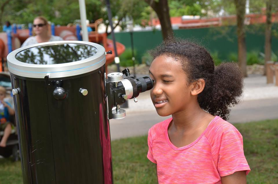 Student looking through a telescope