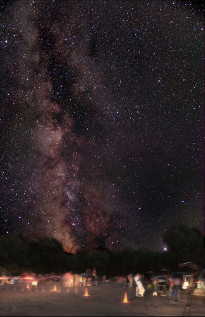 View of the Milky Way with amateur astronomers setting up telescopes